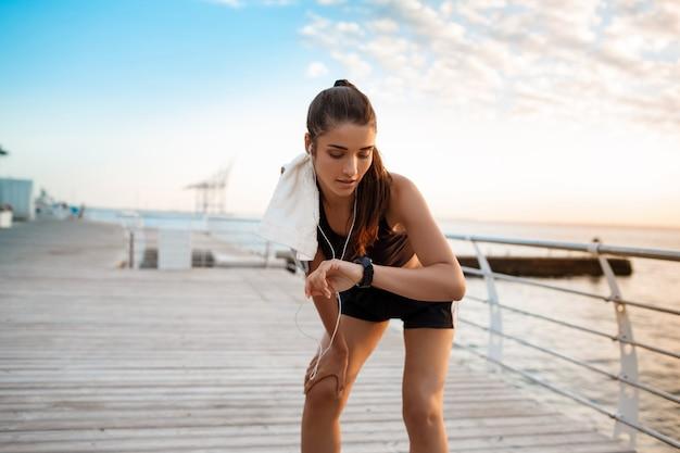 Linda garota esportiva, olhando para o relógio durante o nascer do sol sobre a beira-mar.