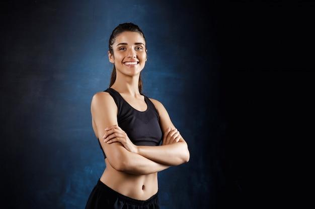 Linda garota esportiva posando com os braços cruzados sobre parede escura.