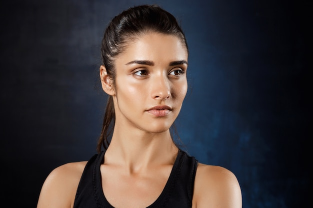 Linda garota esportiva posando sobre parede escura.