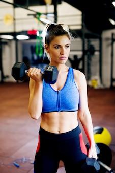 Linda garota esportiva praticando com um haltere no ginásio.