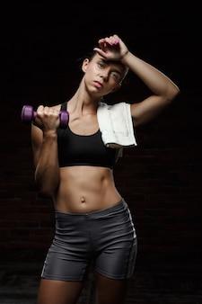 Linda garota esportiva treinando sobre parede escura