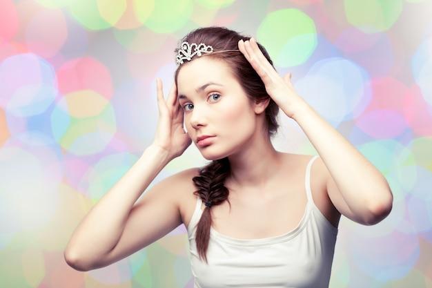 Linda garota está colocando um diadema de diamante e se admirando
