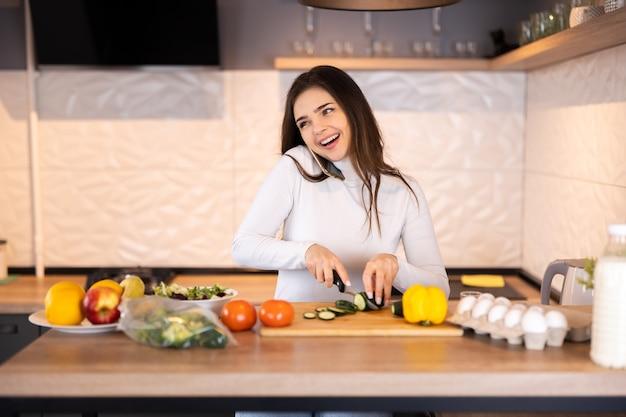 Linda garota está cortando legumes para salada, falando ao telefone celular e sorrindo enquanto cozinha na cozinha em casa.