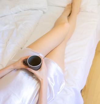 Linda garota está deitada na roupa de cama branca no interior minimalista do apartamento cinza. mulher jovem com manto de seda está bebendo café. café da manhã aconchegante.