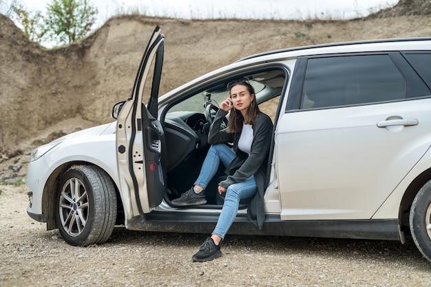Linda garota está descansando fora da cidade e posando perto do carro