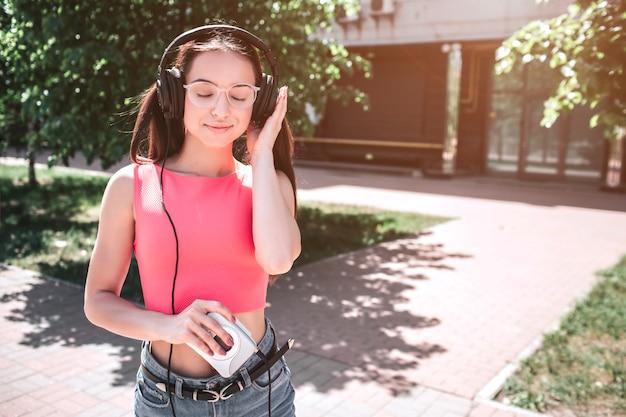 Linda garota está do lado de fora e ouvindo música em fones de ouvido. ela está segurando o tocador pequeno e branco na mão direita e pressionando a outra mão no fone de ouvido. ela gosta de ouvir música.