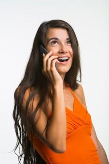 Linda garota está falando pelo celular. coquete senhora está olhando com emocionante sobre fundo branco.