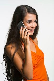 Linda garota está falando pelo celular. feliz senhora está olhando com emocionante sobre fundo branco.