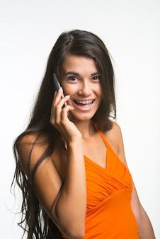 Linda garota está falando pelo celular. senhora feliz está olhando com emocionante sobre fundo branco.