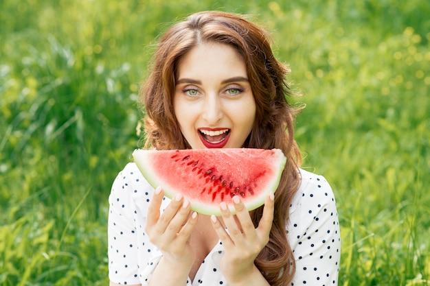Linda garota está mordendo a fatia de melancia na grama