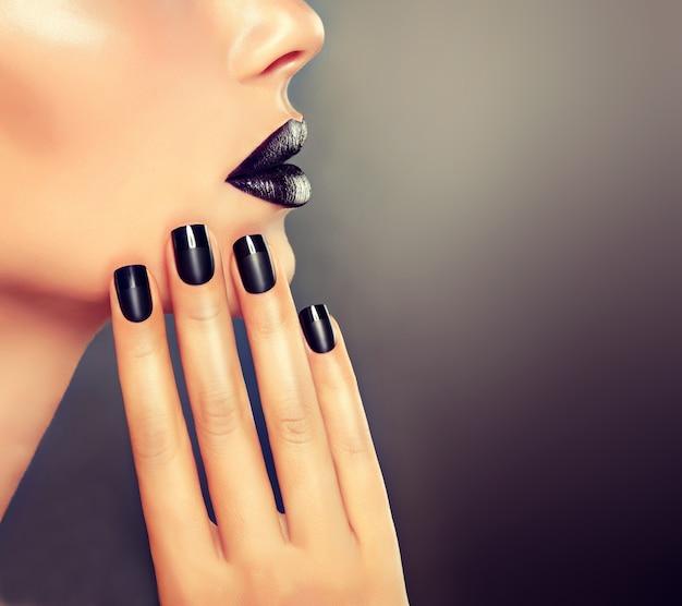 Linda garota está mostrando manicure preta nas unhas na frente dos lábios bem formados pintados de preto. detalhe do close up. maquiagem, cosmética e manicure.
