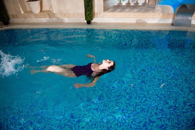 Linda garota está nadando na piscina