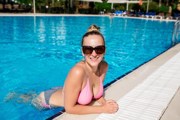 Linda garota está nadando na piscina.