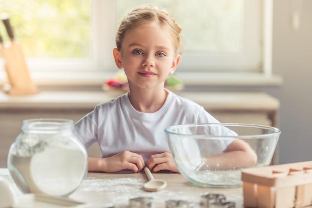 Linda garota está olhando para a câmera e sorrindo enquanto cozinha