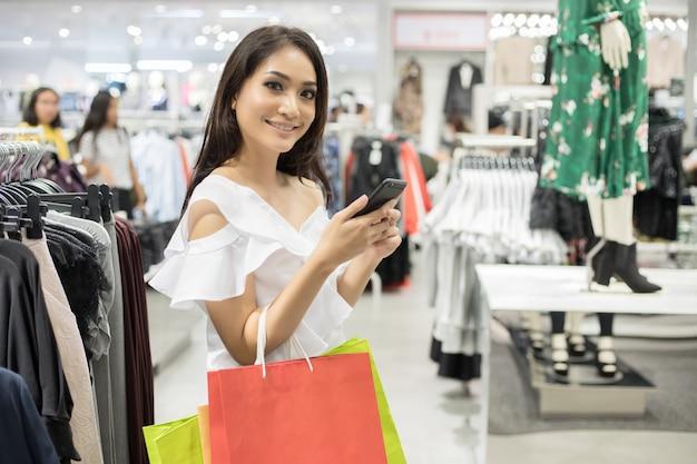 Linda garota está segurando sacolas de compras e usando um telefone inteligente e sorrindo enquanto fazia compras