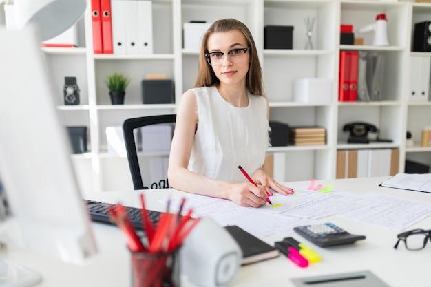 Linda garota está sentada à mesa no escritório, segurando uma caneta na mão