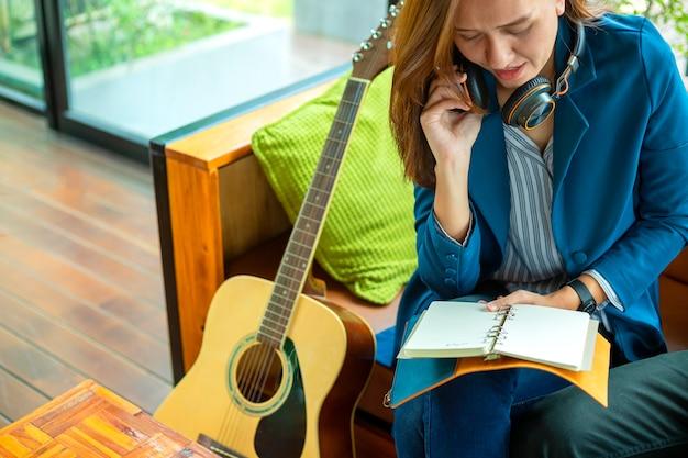 Linda garota está tocando guitarra pela janela. estilo de vida de educação relaxar conceito