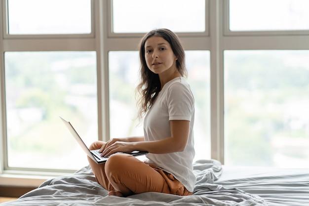 Linda garota está trabalhando no laptop enquanto está sentado em uma cama por uma janela panorâmica com uma bela vista de um andar alto. interior moderno e elegante. um local de trabalho acolhedor. compras na internet.