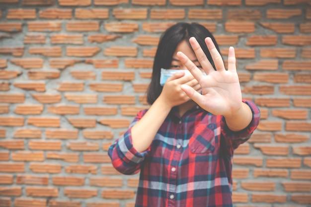 Linda garota está usando máscara e fazendo a mão parada de outra parede de parede propick onb rick