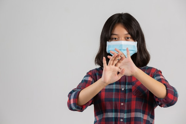 Linda garota está usando máscara e fazendo parar a mão de outro prople na parede branca.