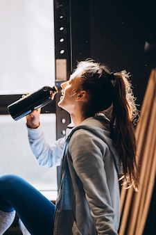 Linda garota estava bebendo água de uma garrafa de plástico, manhã ensolarada e quente