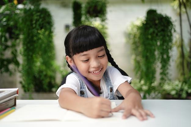 Linda garota estudante asiática desenhando e escrevendo no livro para a lição de casa em casa.