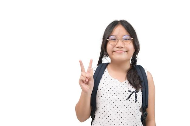 Linda garota estudante sorri e mostra um sinal de vitória, isolado no fundo branco. educação, sucesso e conceito de escola. copie o espaço.