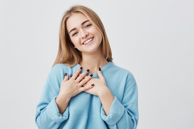 Linda garota européia de aparência amigável positiva com um sorriso sincero adorável, sentindo-se grata e agradecida, mostrando seu coração cheio de amor e gratidão, segurando as mãos no peito