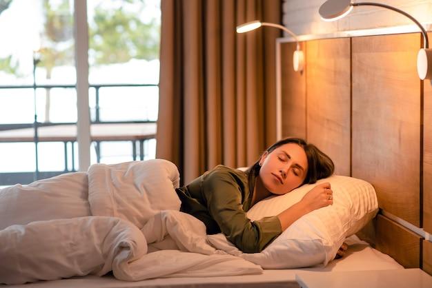 Linda garota europeia dormindo na cama no quarto. jovem mulher com cabelo castanho usa pijama e deitada sob a luz da lâmpada. conceito de descanso. interior moderno do apartamento. hora da manhã