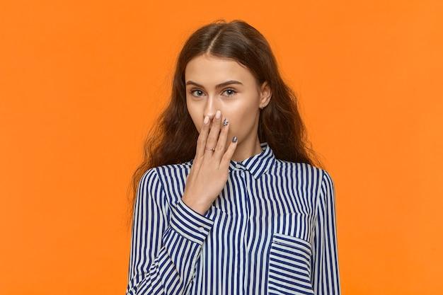 Linda garota europeia esbelta com cabelo escuro encaracolado, posando para uma parede laranja com a mão nos lábios