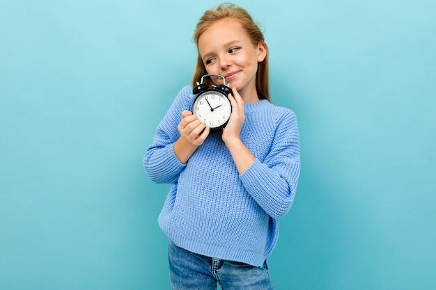 Linda garota europeia segurando um despertador nas mãos de uma parede de azul claro