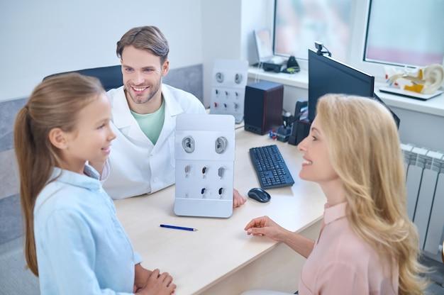 Linda garota experimentando um novo aparelho surdo na frente de sua mãe sorridente e um médico satisfeito