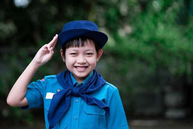 Linda garota exploradora de uniforme levanta três dedos para respeitar com alegria e sorriso
