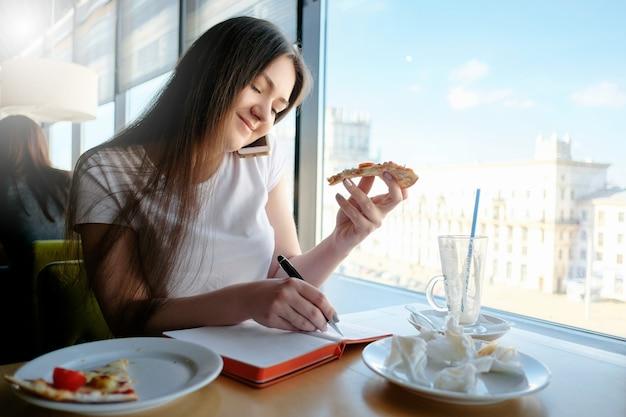 Linda garota falando em um café ao telefone, come pizza e escreve em um diário, vários casos ao mesmo tempo, pratos sujos na mesa