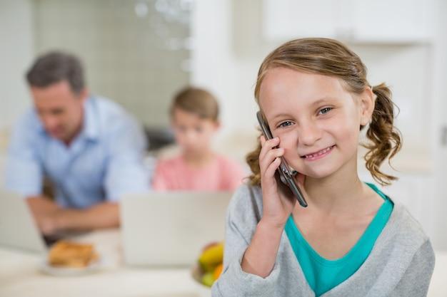 Linda garota falando no celular na cozinha
