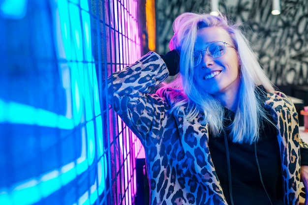 Linda garota fashion sentado no bar perto da parede de néon
