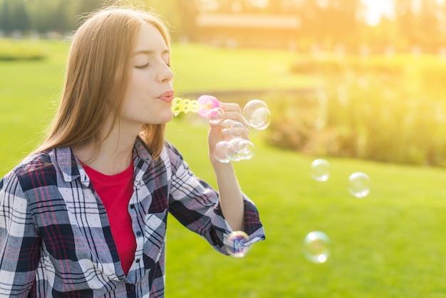 Linda garota fazendo bolhas de sabão