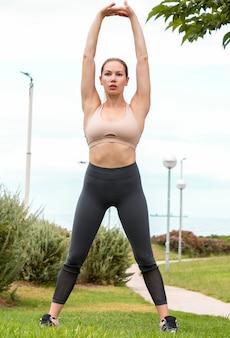 Linda garota fazendo exercício físico com as pernas na largura dos ombros e braços para cima