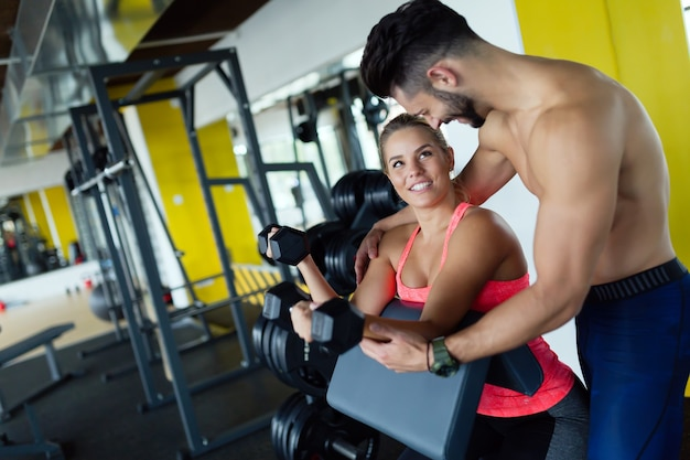 Linda garota fazendo exercícios na academia com o personal trainer