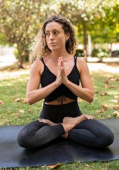 Linda garota fazendo ioga em um parque da cidade