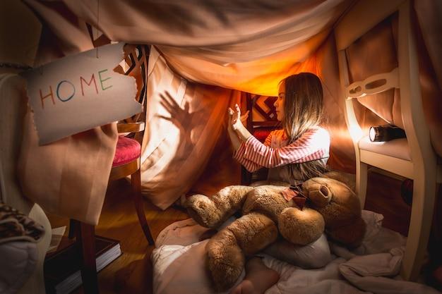 Linda garota fazendo teatro de sombras em casa feita por si mesma no quarto
