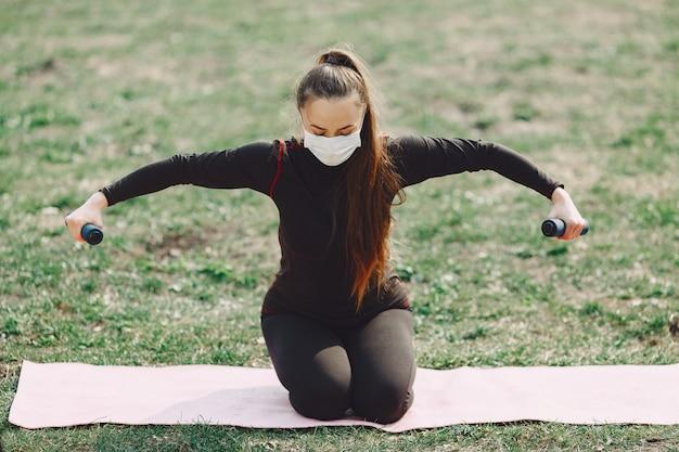 Linda garota fazendo yoga em um parque de verão