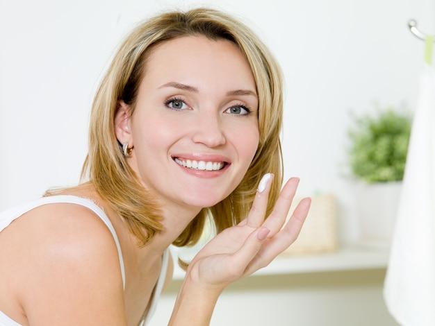 Linda garota feliz aplicando creme hidratante no rosto em pé no banheiro