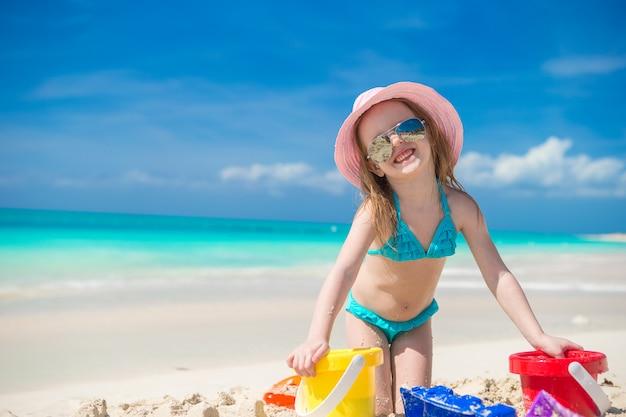 Linda garota feliz brincando com brinquedos na praia de férias