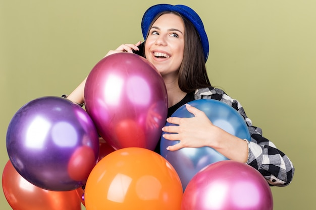 Linda garota feliz com chapéu azul atrás de balões falando ao telefone