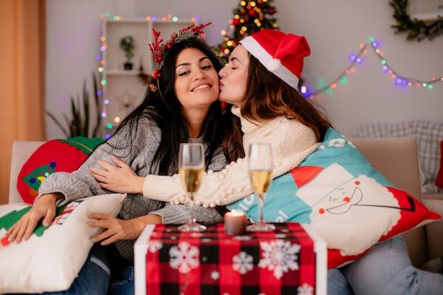 Linda garota feliz com chapéu de papai noel beija a amiga com coroa de azevinho sentada nas poltronas e aproveitando o natal em casa