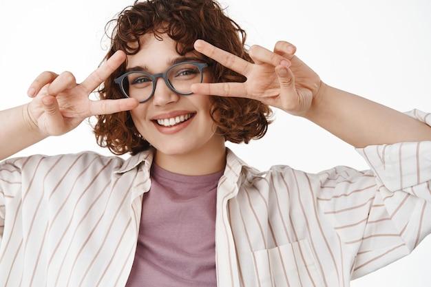 Linda garota feliz com dentes brancos, sorriso alegre e sinal-v da paz kawaii perto dos olhos, de pé positivo e alegre no branco