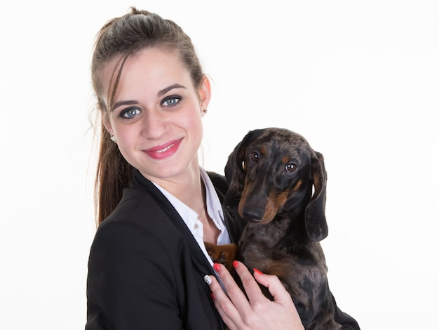 Linda garota feliz com longos cabelos escuros segurando cachorro pequeno