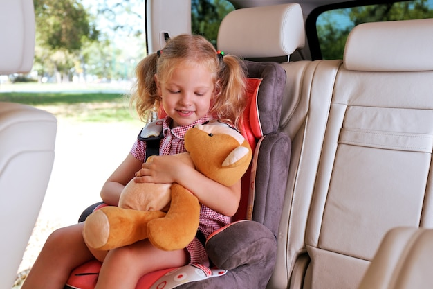 Linda garota feliz com o ursinho de pelúcia sentado no carro