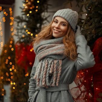 Linda garota feliz com roupas da moda vintage em malhas com um chapéu e um lenço estiloso nas férias de natal